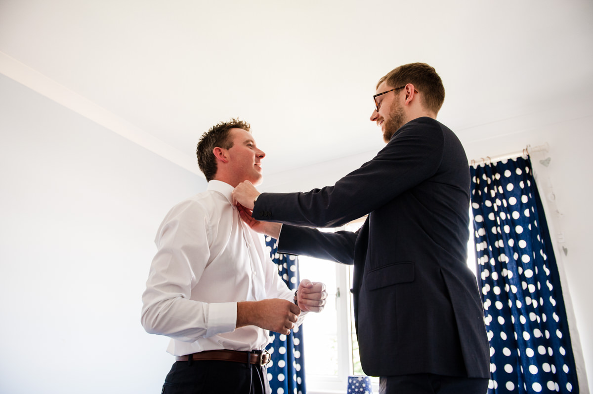 brother helping from with wedding tie