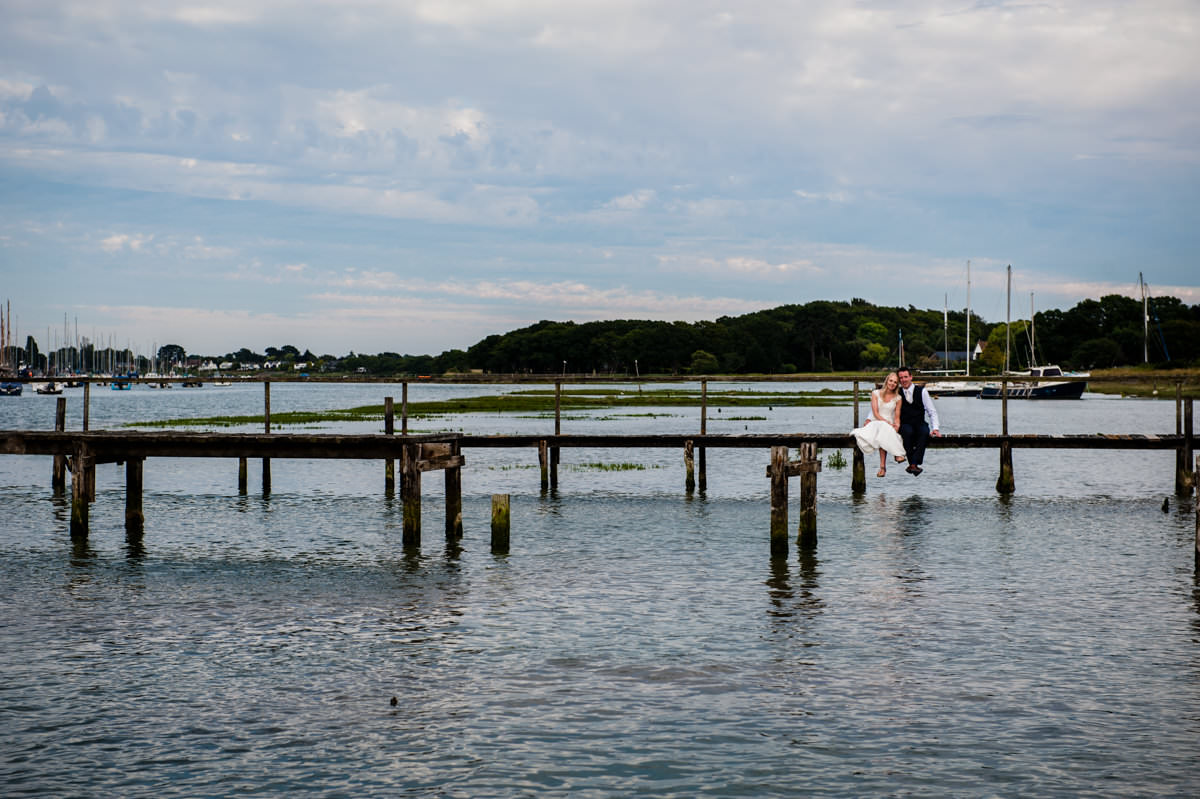 Gorgeous photo of bride and groom on jetty at Itchenor Sailing Club wedding