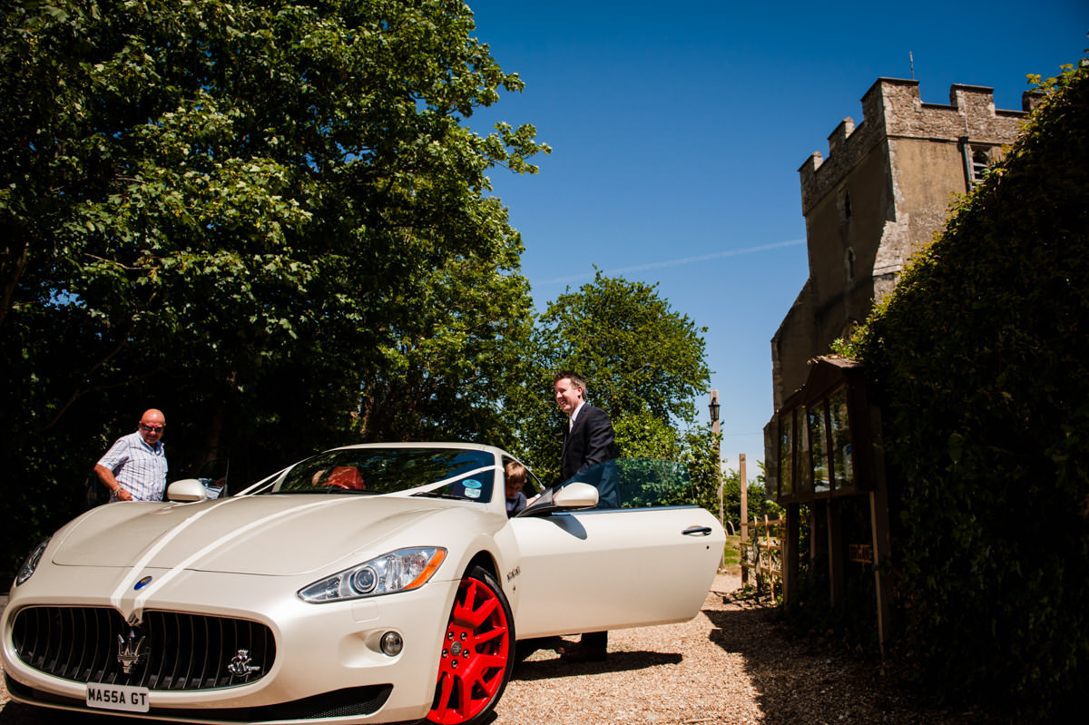 groom arrives in style in a wedding maserati