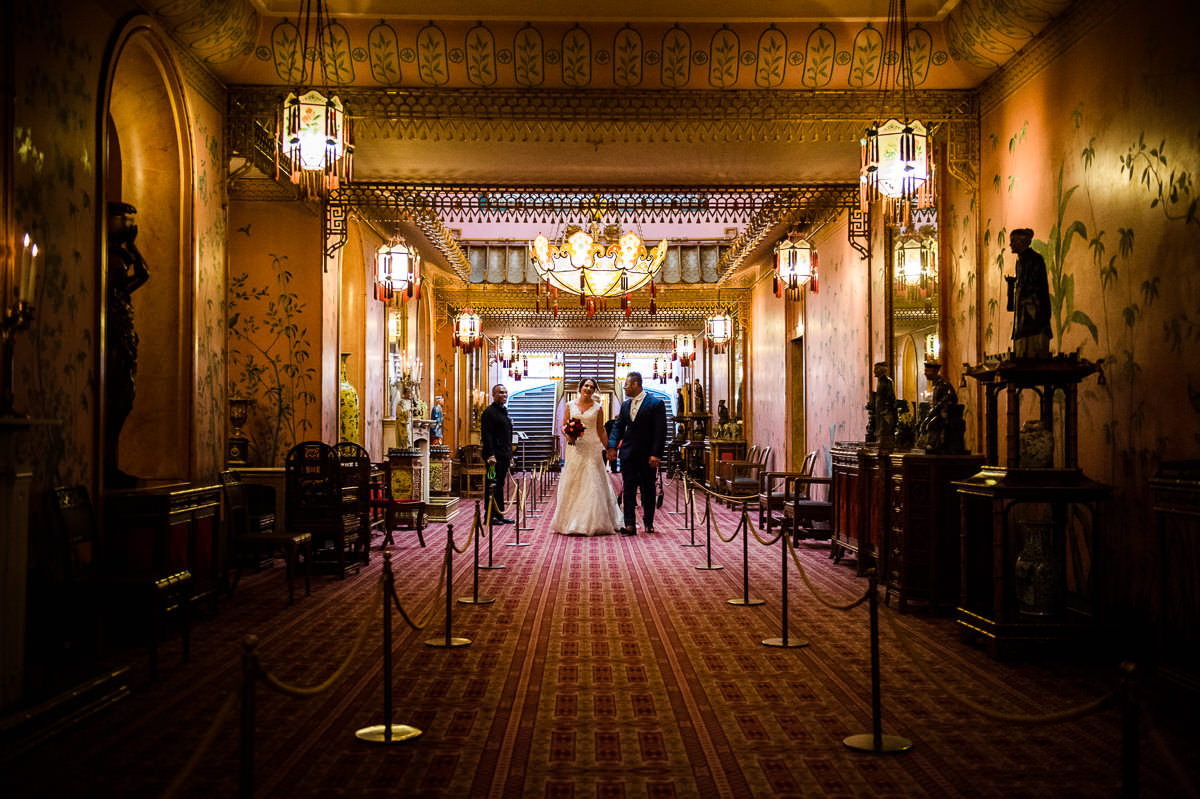 Newlyweds walking hand in hand along the corridors of the Royal Pavilion in Brighton