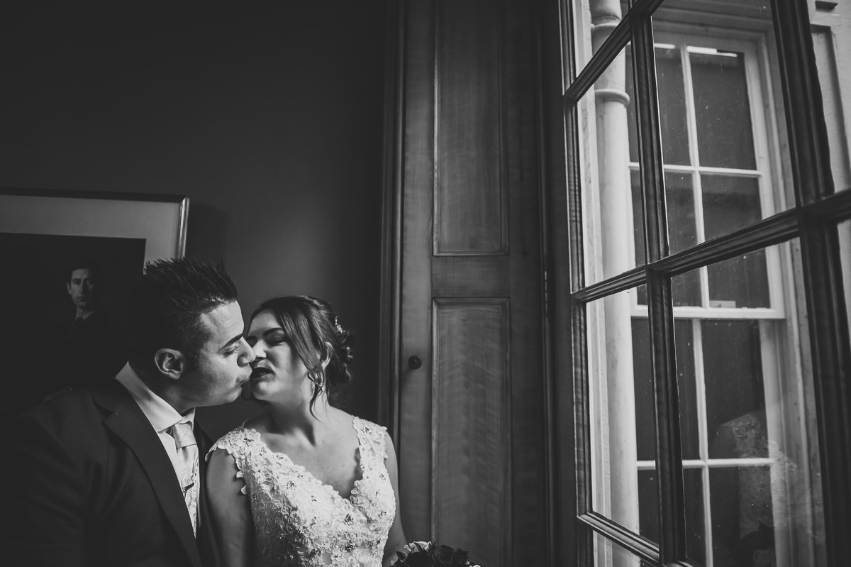 Bride and Groom kissing at the door of the pavilion