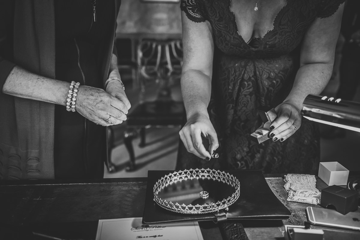 Brides mum and sister putting wedding rings on tray