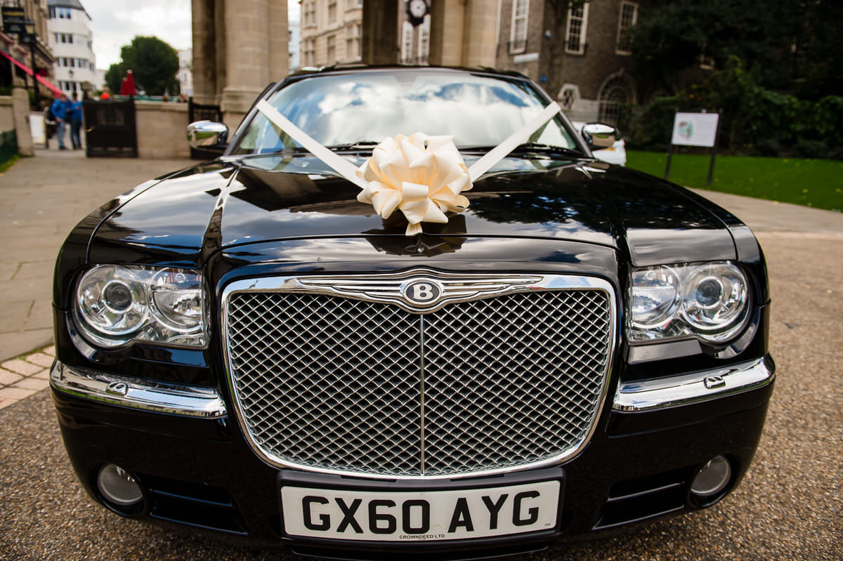 Black bentley arrives with bride and groom ready for their brighton pavilion wedding ceremony