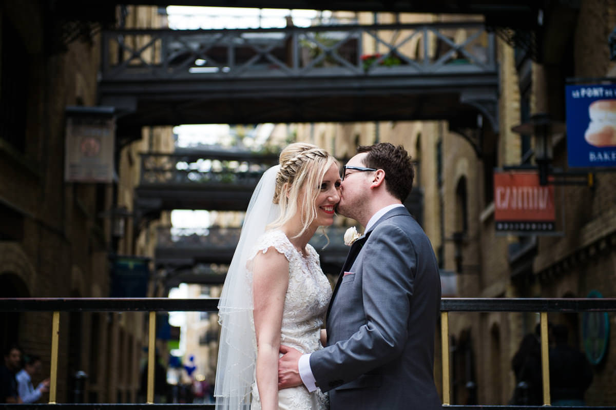 bride and groom kissing along shad thames near the design museum