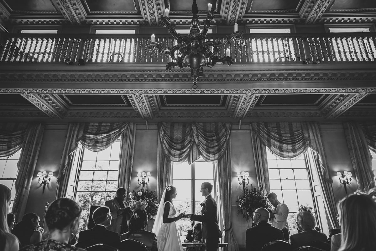 bride and groom exchanging vows at their hampton court house wedding
