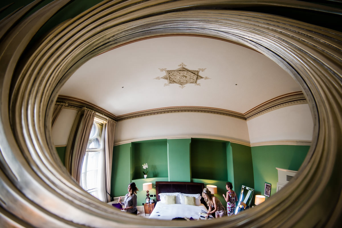 Reflection in bedroom mirror of bride and bridesmaids getting ready at St Pancras Renaissance Hotel, London