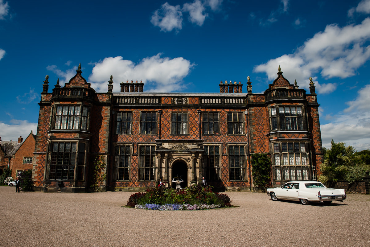 Bride & Groom arriving at their Arley Hall & Gardens Wedding in a Chevrolet